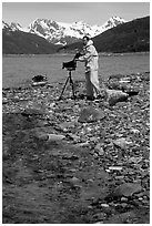 Large format photographer wearing kayaking gear on a beach in East Arm. Glacier Bay National Park, Alaska (black and white)