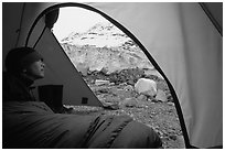Camper lying in sleeping bag looks at Lamplugh Glacier. Glacier Bay National Park, Alaska (black and white)