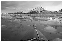 Kayak's prow, floating icebergs, and glacier. Glacier Bay National Park, Alaska (black and white)