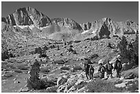 Hikers on alpine terrain and Mt Giraud range, Dusy Basin. Kings Canyon National Park, California (black and white)