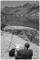 Hiker looking at map in front of lake, lower Dusy Basin. Kings Canyon National Park, California (black and white)