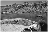 Hiker with map near lake, lower Dusy Basin. Kings Canyon National Park, California (black and white)