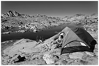 Man sitting in tent above lake, Dusy Basin. Kings Canyon National Park, California (black and white)