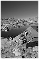 Man looking out from tent above lake, morning, Dusy Basin. Kings Canyon National Park, California (black and white)