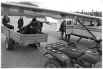Unloading the gear from the plane to a trailer on the Port Alsworth airstrip. Lake Clark National Park, Alaska (black and white)