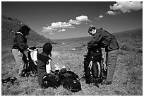 Backpackers breaking camp and readying backpacks. Lake Clark National Park, Alaska (black and white)