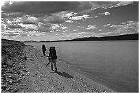 Backpackers walking on the shore of Turquoise Lake. Lake Clark National Park, Alaska (black and white)
