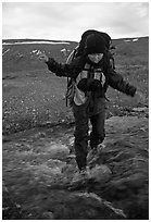 Backpacker balancing herself while crossing a stream. Lake Clark National Park, Alaska (black and white)