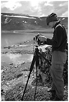 Large format photographer with camera on the shores of Turquoise Lake. Lake Clark National Park, Alaska (black and white)