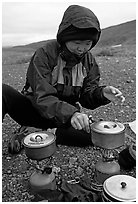 Backpacker cooks meal on gas campstove. Lake Clark National Park, Alaska (black and white)