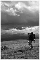 Backpacker seen from the side walking fast in the tundra. Lake Clark National Park, Alaska (black and white)