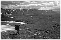 Backpackers walking down on a carpet of alpine flowers towards Twin Lakes. Lake Clark National Park, Alaska (black and white)
