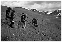 Backpackers with big packs going down a slope. Lake Clark National Park, Alaska (black and white)