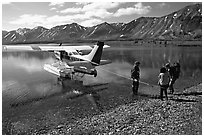 Backpackers being picked up by floatplane at Twin Lakes. Lake Clark National Park, Alaska (black and white)