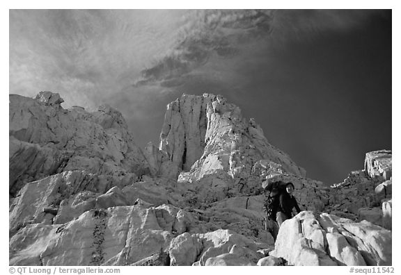 Looking up to woman scrambling on rocks on the East face of Mt Whitney. Sequoia National Park, California