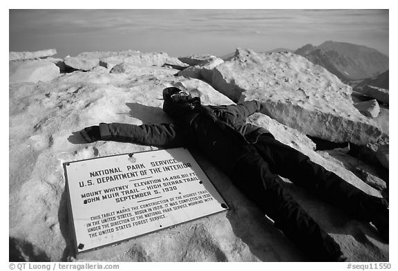 Hiker laying exhausted on Mt Whitney summit sign. Sequoia National Park, California