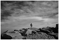 Hiker standing on flat rocks on top of Mt Whitney summit. Sequoia National Park, California (black and white)