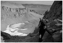 Woman with backpack pausing on steep terrain above Iceberg Lake. Sequoia National Park, California (black and white)