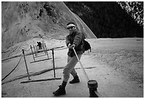 Hiker and cables on the regular route to Half-Dome. Yosemite National Park, California (black and white)