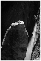 Climber resting on top of Lost Arrow spire with Yosemite Falls behind. Yosemite National Park, California (black and white)