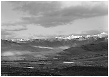 Tarn lakes, tundra, and snowy mountains of Alaska Range with patches of light. Denali National Park ( black and white)