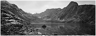 Mineral landscape with scree, rocky peaks, and lake. Gates of the Arctic National Park (Panoramic black and white)