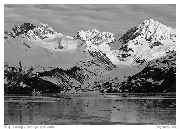 Coastal mountains with glacier dropping into icy fjord. Glacier Bay National Park (black and white)
