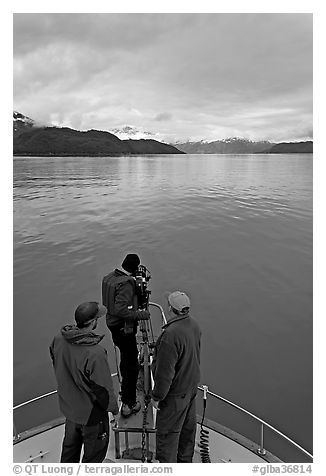 Film crew working on the bow of a small boat. Glacier Bay National Park (black and white)