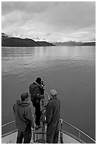 Film crew working on the bow of a small boat. Glacier Bay National Park ( black and white)