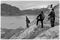 Film crew carrying a motion picture camera down rocky slopes. Glacier Bay National Park ( black and white)