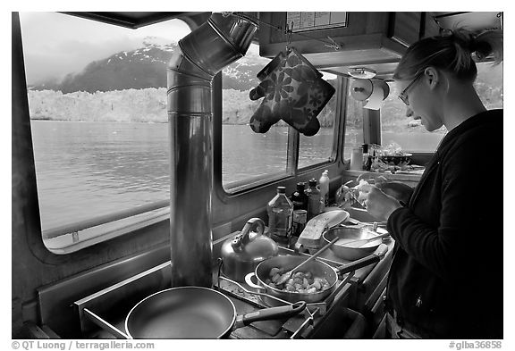 Woman preparing a breakfast aboard small tour boat. Glacier Bay National Park (black and white)