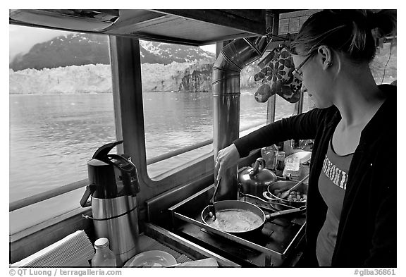 Woman cooking eggs aboard small tour boat, with glacier in view. Glacier Bay National Park (black and white)