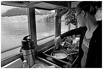 Woman cooking eggs aboard small tour boat, with glacier in view. Glacier Bay National Park, Alaska, USA. (black and white)