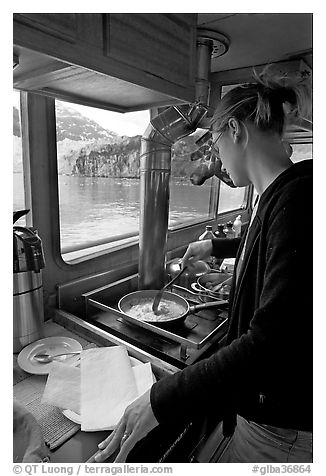 Woman cooking eggs aboard small tour boat, with glacier outside. Glacier Bay National Park (black and white)