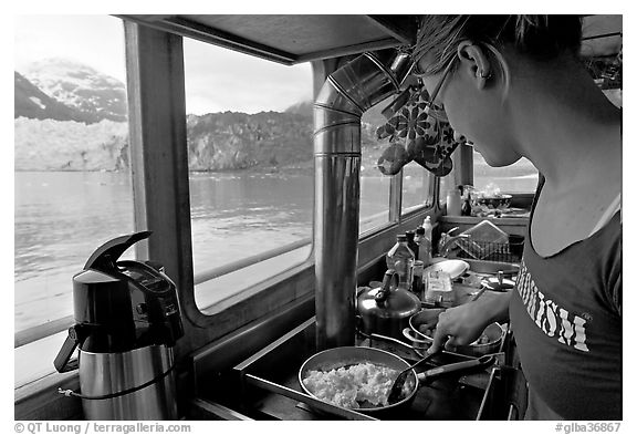 Woman prepares breakfast eggs aboard small tour boat, with glacier in view. Glacier Bay National Park (black and white)