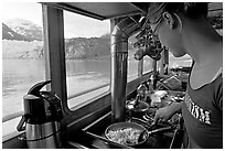 Woman prepares breakfast eggs aboard small tour boat, with glacier in view. Glacier Bay National Park, Alaska, USA. (black and white)