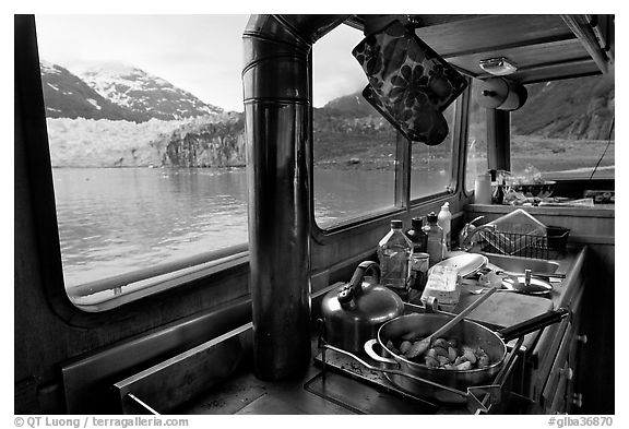 Breakfast potatoes in a small boat moored in front of glacier. Glacier Bay National Park (black and white)