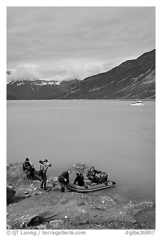 Film crew embarking on a skiff after shore excursion. Glacier Bay National Park (black and white)