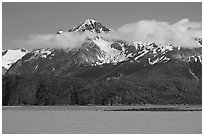 Snowy peaks and clouds raising above turquoise waters in sunny weather. Glacier Bay National Park, Alaska, USA. (black and white)
