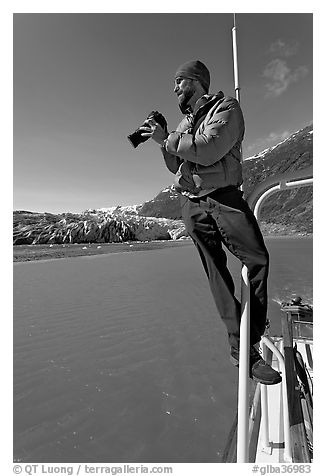 Photographer perched on boat in Reid Inlet. Glacier Bay National Park (black and white)