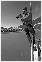Photographer perched on boat in Reid Inlet. Glacier Bay National Park, Alaska, USA. (black and white)