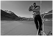 Photographer perched on boat with Reid Glacier behind. Glacier Bay National Park, Alaska, USA. (black and white)