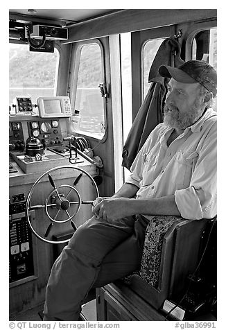 Captain sitting at the wheel. Glacier Bay National Park, Alaska, USA.