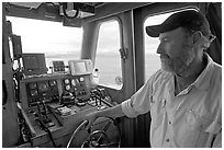 Captain steering boat with navigation instruments. Glacier Bay National Park ( black and white)