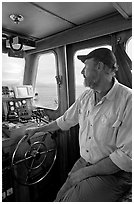 Captain steering boat using navigation instruments. Glacier Bay National Park, Alaska, USA. (black and white)