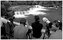 Photographers on observation platform and Brooks falls with bears. Katmai National Park, Alaska, USA. (black and white)
