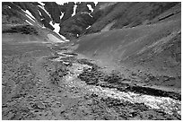 Stream flows from verdant hills into  barren valley floor. Katmai National Park, Alaska, USA. (black and white)