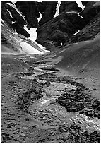 Stream flows from the verdant hills into the barren floor of the Valley of Ten Thousand smokes. Katmai National Park ( black and white)
