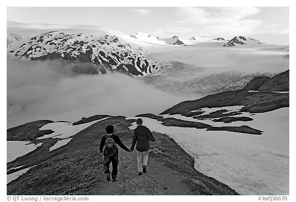 Couple hiking down Harding Icefied trail, late afternoon. Kenai Fjords National Park (black and white)