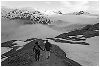 Couple hiking down Harding Icefied trail, late afternoon. Kenai Fjords National Park, Alaska, USA. (black and white)
